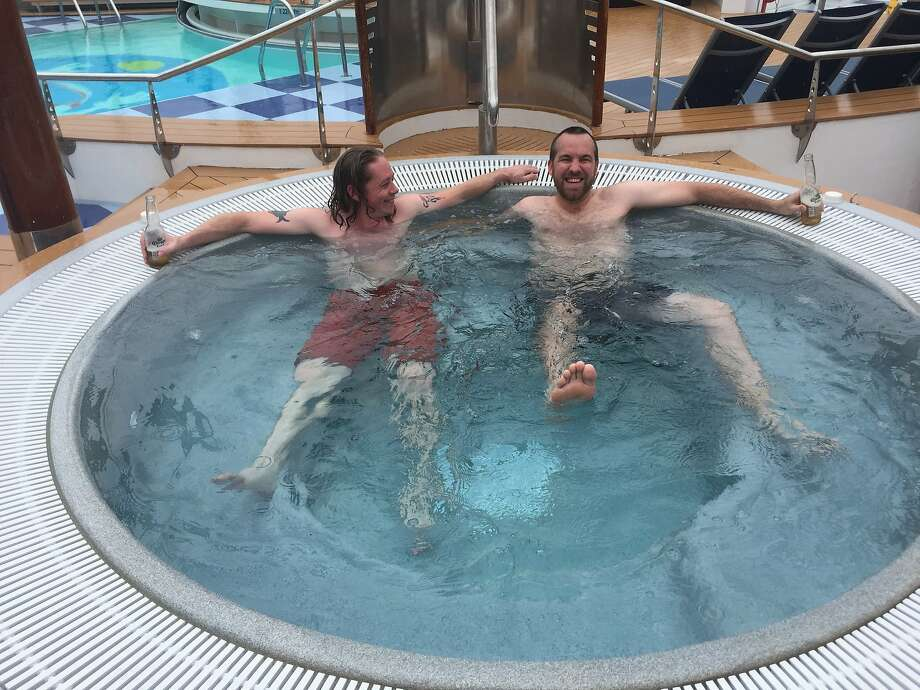 Tech executives John McKenney and Kris Taylor, of Philadelphia, lounge in the hot tub on the lido deck of Salesforce's floating Dream Boat hotel on Wednesday, Sept. 16, 2015. In spite of the cold and the rain, the two insisted on creating a cruise-like experience for themselves. Photo: Marissa Lang