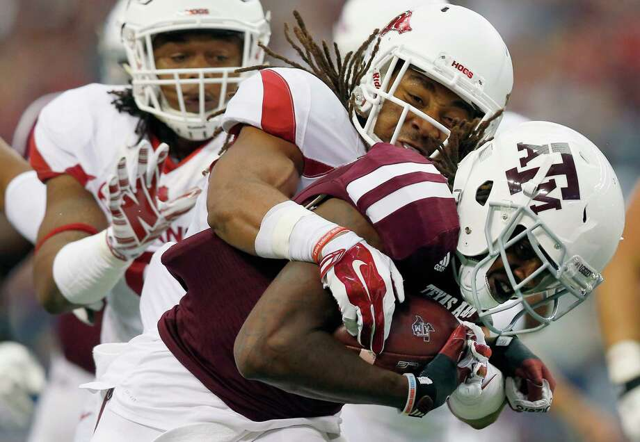 Brandon Williams of the Texas A&M Aggies carries the ball to score a touchdown against Deatrich Wise (left) and Alan Turner of the Arkansas Razorbacks in the first half at AT&T Stadium on Sept. 27, 2014 in Arlington. Photo: Tom Pennington /Getty Images / 2014 Getty Images