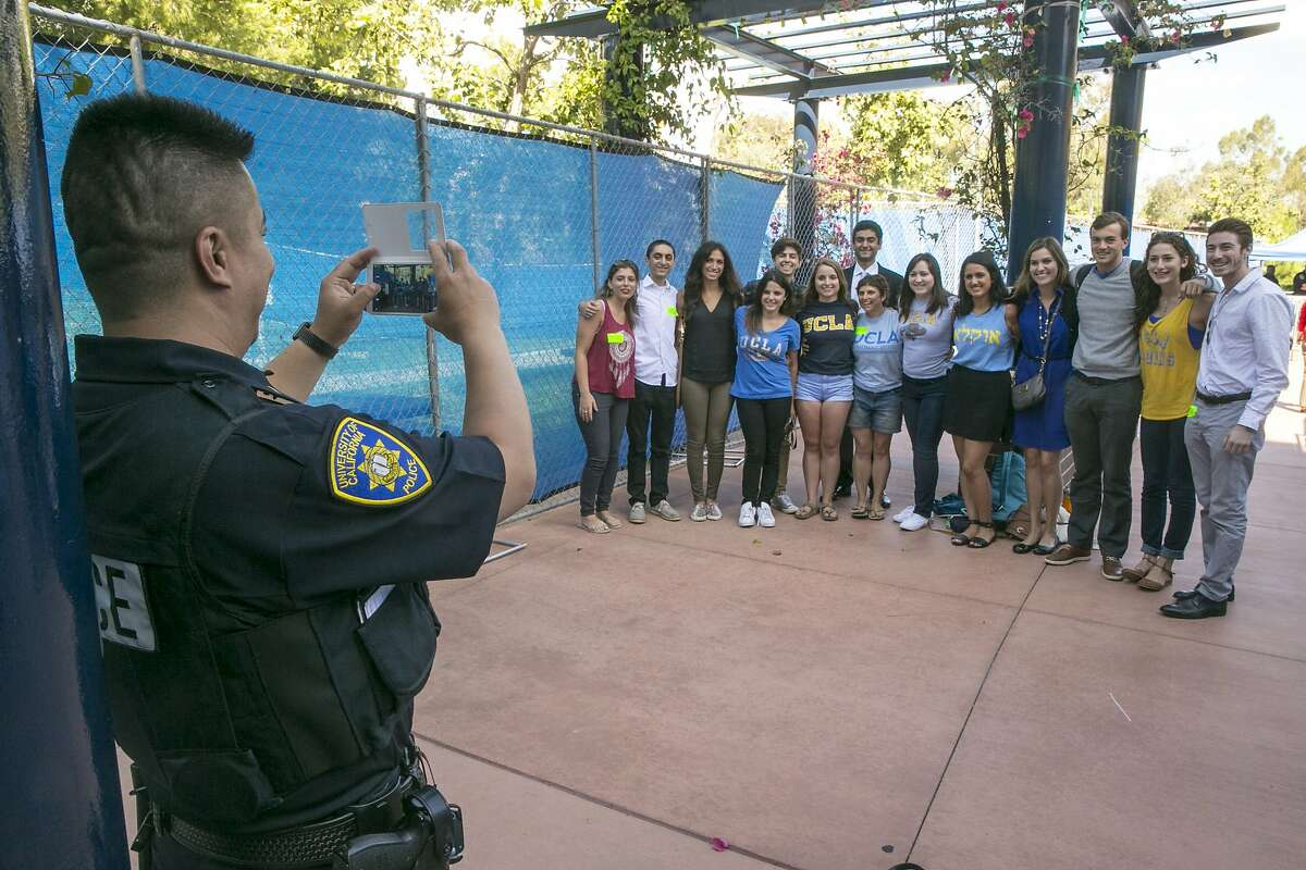 UCLA Students Against Anti Semitism have their group photo taken by University of California Irvine campus police officer Mark Zuasola, left, after a University of California's Board of Regents meeting at the Student Center to discuss a controversial policy statement on intolerance in Irvine, Calif., on Thursday, Sept. 17, 2015. The University of California's first draft of system-wide principles defining intolerance is drawing protests from free-speech advocates who call it censorship and Jewish organizations that say it doesn't go far enough to protect against anti-Semitism. (AP Photo/Damian Dovarganes)