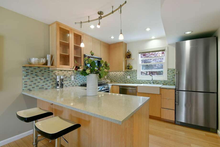 Modern fixtures, translucent tile backsplash, bamboo cabinetry and Caesarstone counters highlight the modern chef's kitchen.  Photo: OpenHomesPhotography.com