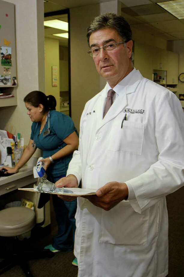 Clive Fields, M.D., of Village Family Practice. In the background is medical assistant, Alma Fores. (For the Chronicle/Gary Fountain, September 15, 2015) Photo: Gary Fountain, Freelance / Copyright 2015 by Gary Fountain