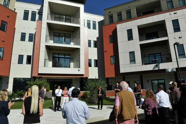 People gather for the ribbon cutting at the new 2 West Ave Apartment Community, seen here on Thursday, Sept. 17, 2015, in Saratoga Springs, N.Y.  There are 63 total units, consisting of either one, two or three bedrooms.  Six of the units are town house, three bedroom, two and a half bath units.  There is also commercial space on  the ground floor and on Thursday is was announced that 2 West Bar and Grille and 2 West Express will occupy one of the commercial spaces.  The bar and grille will feature all natural burgers, hand-tossed pizzas and New York craft beers.  2 West Express will feature healthy, quick made-to-order items, like salads and wraps and artisanal pizzas.  Developers are still looking for a business to occupy the second commercial space.   (Paul Buckowski / Times Union) Photo: PAUL BUCKOWSKI / 00033345A