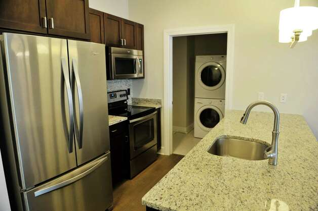 A view of the kitchen and laundry room inside a one-bedroom unit at the new 2 West Ave Apartment Community, seen here on Thursday, Sept. 17, 2015, in Saratoga Springs, N.Y.  There are 63 total units, consisting of either one, two or three bedrooms.  Six of the units are town house, three bedroom, two and a half bath units.  There is also commercial space on  the ground floor and on Thursday is was announced that 2 West Bar and Grille and 2 West Express will occupy one of the commercial spaces.  The bar and grille will feature all natural burgers, hand-tossed pizzas and New York craft beers.  2 West Express will feature healthy, quick made-to-order items, like salads and wraps and artisanal pizzas.  Developers are still looking for a business to occupy the second commercial space.   (Paul Buckowski / Times Union) Photo: PAUL BUCKOWSKI / 00033345A
