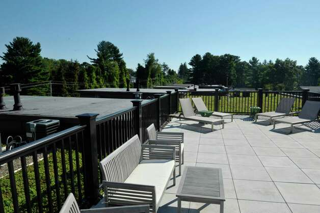 A view of the green roof with seating at the new 2 West Ave Apartment Community, seen here on Thursday, Sept. 17, 2015, in Saratoga Springs, N.Y.  There are 63 total units, consisting of either one, two or three bedrooms.  Six of the units are town house, three bedroom, two and a half bath units.  There is also commercial space on  the ground floor and on Thursday is was announced that 2 West Bar and Grille and 2 West Express will occupy one of the commercial spaces.  The bar and grille will feature all natural burgers, hand-tossed pizzas and New York craft beers.  2 West Express will feature healthy, quick made-to-order items, like salads and wraps and artisanal pizzas.  Developers are still looking for a business to occupy the second commercial space.   (Paul Buckowski / Times Union) Photo: PAUL BUCKOWSKI / 00033345A