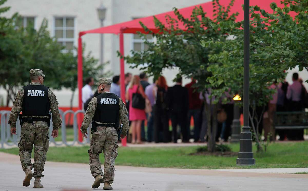 Military police officers walk near a gathering of media during a briefing before Sgt. Bowe Bergdahl's Article 32 hearing at Joint Base San Antonio - Fort Sam Houston on Thursday, Sept. 17, 2015. Bergdahl is charged with deserting his post and misbehavior before the enemy. He vanished from his post more than six years ago and was captured by the Taliban, who held him prisoner for five years. (Kin Man Hui/San Antonio Express-News)