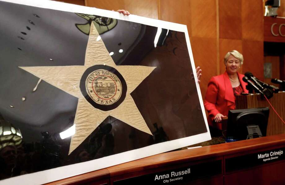 Mayor Annise Parker shown with a 1915 prototype for the City of Houston flag at a press conference in the City Council Chambers of Houston City Hall Wednesday, Sept. 9, 2015, in Houston, Texas. The City of Houston, Preservation Houston and the North American Vexillogical Association (NAVA) announced the restoration of the flag. The prototype was made by the seamstresses at Levy Bros. department store and then sent to New York where it served as the model for the official silk flag. ( Gary Coronado / Houston Chronicle ) Photo: Gary Coronado, Staff / © 2015 Houston Chronicle
