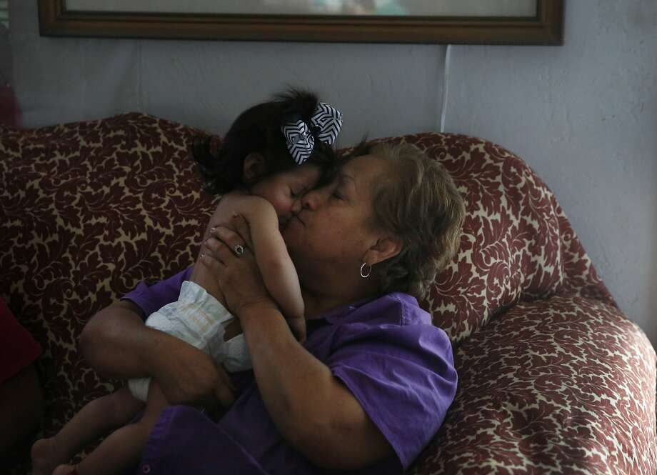 Andrea Lopez, 67, kisses her 8-month-old granddaughter, Carissa, while trying to get her to take a nap. She took Carissa's clothes off to keep her cool. The Lopez home in Fresno ran out of water when their well went dry in February and so they can't use their swamp cooler. Photo: Leah Millis, The Chronicle