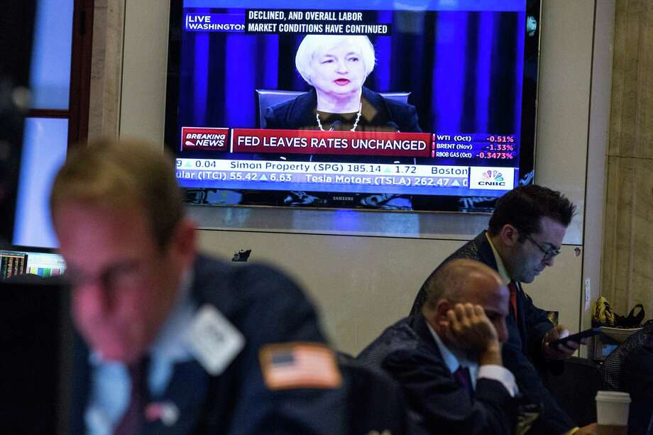 A trader works on the floor of the New York Stock Exchange while Federal Reserve Chairwoman Janet Yellen explains why the Federal Reserve chose not raise interest rates. Traders had speculated for weeks over whether the fed would raise rates or keep them at near zero percent interest. Photo: Andrew Burton /Getty Images / 2015 Getty Images