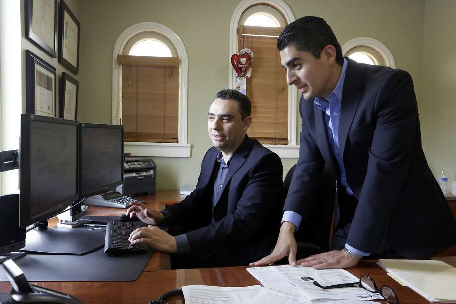 Certified financial planners Aaron Munoz (left) and Gilbert Cerda offer advice with a focus on the Hispanic population. Photo: Damian Dovarganes, Associated Press