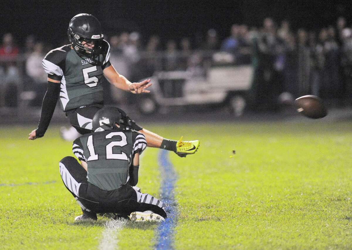 Schalmont's Anthony Yezzo (12) holds as Jake Defayette (5) kicks an extra point against Burnt Hills-Ballston Lake during the first half of their Section II football game on Friday, Sept. 26, 2014, in Rotterdam, N.Y., (Hans Pennink / Special to the Times Union) ORG XMIT: HP115