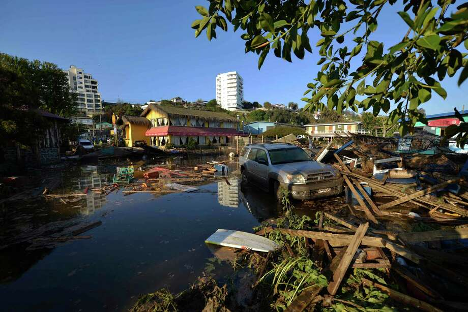 A car is surrounded by debris in a flooded street after an earthquake-triggered tsunami hit Concon, Chile. Several coastal towns were flooded from tsunami waves set off by the magnitude-8.3 quake. Photo: Matias Delacroix /Associated Press / AP
