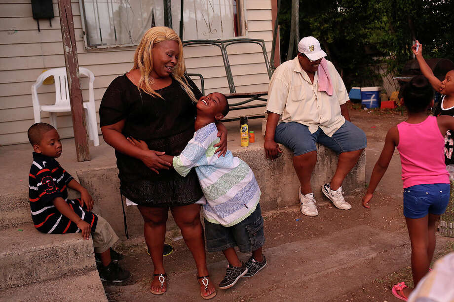 Tamika Winn is embraced by her son, Trezvant Mason, 7, as they spend the evening with their family, as they do most evenings, at the East Side home owned by Winn's grandmother, Gloria Nelson, 88, in July 2014. Photo: Lisa Krantz /San Antonio Express-News / SAN ANTONIO EXPRESS-NEWS