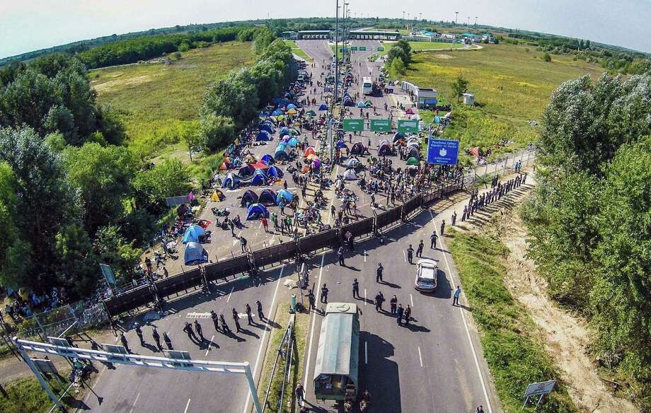 TOPSHOTS An aerial view taken on September 16, 2015 shows migrants camping on no-man's land of the border between Hungary and Serbia near Roeszke. Hungarian police used tear gas and water cannon against migrants to push them from Hungary's territory. AFP PHOTO / ISTVAN RUZSAISTVAN RUZSA/AFP/Getty Images Photo: ISTVAN RUZSA, Stringer / AFP / Getty Images / AFP