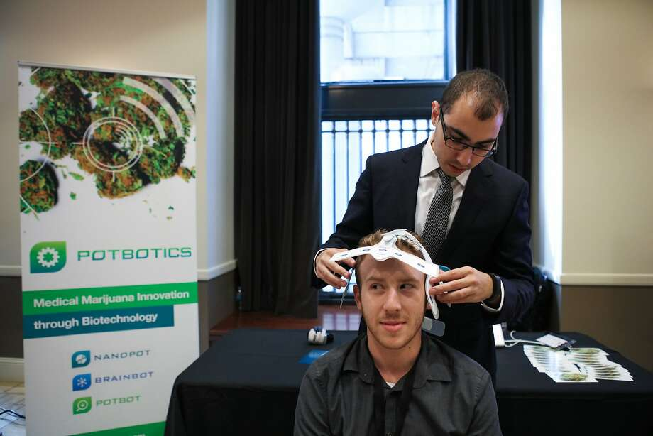 David Goldstein, co-founder and CEO of PotBiotics simulates his product on Eric Cote, at the Cannabis Investor Summit at the Bentley Reserve in downtown San Francisco, California on Thursday, September 17, 2015. PotBiotics aims to study and analyze brain function when stimulated by marijuana. Photo: Gabrielle Lurie, Special To The Chronicle