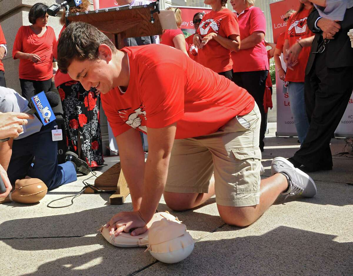 JJ Pesany of Lancaster, 17, demonstrates the CPR technique he learned on as advocates celebrate final step in years-long CPR in schools efforts on the steps of the State Education Building on Thursday, Sept. 17, 2015 in Albany, N.Y. His life was saved by someone doing CPR on him on a football field. (Lori Van Buren / Times Union)