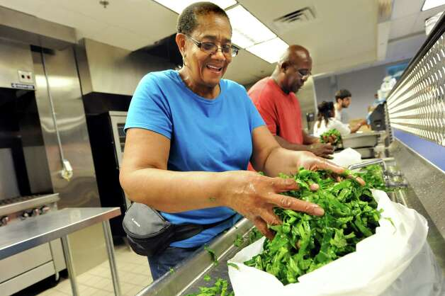 AVillage members Clara Phillips, left, and George York, center, wash and set aside collard greens as they prepare for Mississippi Day on Thursday, Sept. 17, 2015, at Victory Church Dream Center in Albany, N.Y. The 4th annual Mississippi Day in Lincoln Park on Saturday from noon to 8 p.m. (Cindy Schultz / Times Union) Photo: Cindy Schultz / 00033411A