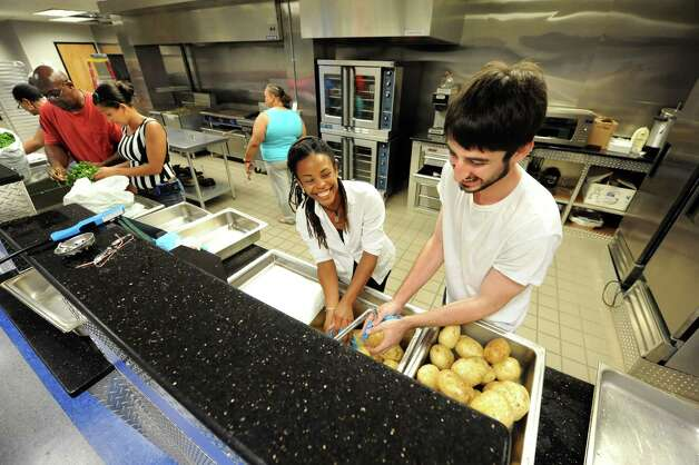 AVillage members Tracian Gordan, center, and Sam Fein, right, have some fun as they wash potatoes in preparation for Mississippi Day on Thursday, Sept. 17, 2015, at Victory Church Dream Center in Albany, N.Y. The 4th annual Mississippi Day in Lincoln Park on Saturday from noon to 8 p.m. (Cindy Schultz / Times Union) Photo: Cindy Schultz / 00033411A