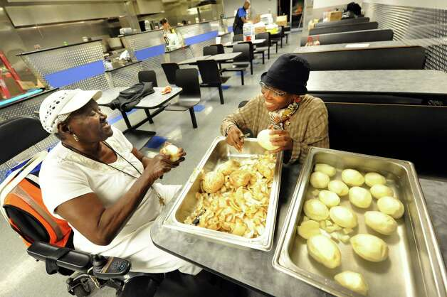 AVilliage members Bessie Thompson, left, and Carol Tyrell chat while they peel potatoes in preparation for Mississippi Day on Thursday, Sept. 17, 2015, at Victory Church Dream Center in Albany, N.Y. The 4th annual Mississippi Day in Lincoln Park on Saturday from noon to 8 p.m. (Cindy Schultz / Times Union) Photo: Cindy Schultz / 00033411A