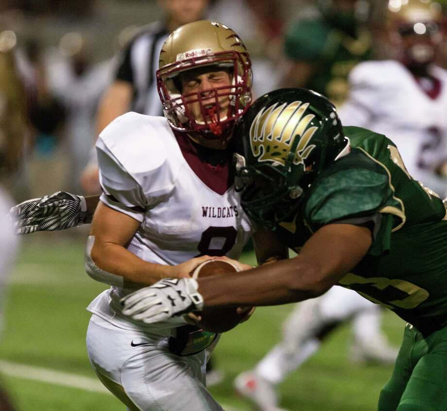 Cypress Woods QB Bryson Powers (8) gets hit hard in the helmet by Cypress Falls LB Blake Thompson (33) during the first half of action between Cy Woods vs Cy Falls high schools during a football game at the Berry Center, Thursday, Sep. 17, 2015, in Spring. ( Juan DeLeon / For the Houston Chronicle ) Photo: Juan DeLeon, For The Chronicle / Houston Chronicle