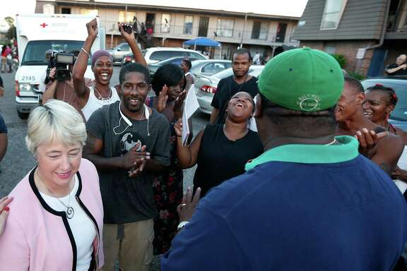 Residents of the Crestmont Apartment Complex, in the 5600 Block of Selinsky, cheer for Mayor Annise Parker, who announced that the city was intervening after the landlord has refused to pay the electricity bill.