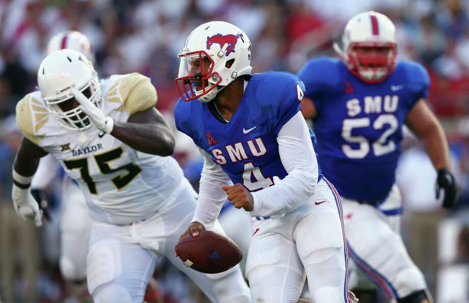 Although a quarterback, Matt Davis, right, has led SMU in rushing in nine consecutive games and topped 100 yards in each of the last three. Photo: Tom Pennington, Staff / 2015 Getty Images