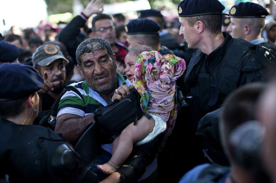 A man carrying a baby is let through a police cordon amid scuffles between migrants and Croatian police officers in Tovarnik, Croatia, Thursday, Sept. 17, 2015. Hundreds of migrants have pushed through police lines in the eastern Croatian town of Tovarnik,  with people trampling and falling on each other amid the chaos, as more than 2,000 men, women and children were stuck at the local train station for hours in blazing heat and sun on Thursday, waiting to board trains and buses for transport to refugee centers. (AP Photo/Marko Drobnjakovic) ORG XMIT: XMD105 Photo: Marko Drobnjakovic / AP
