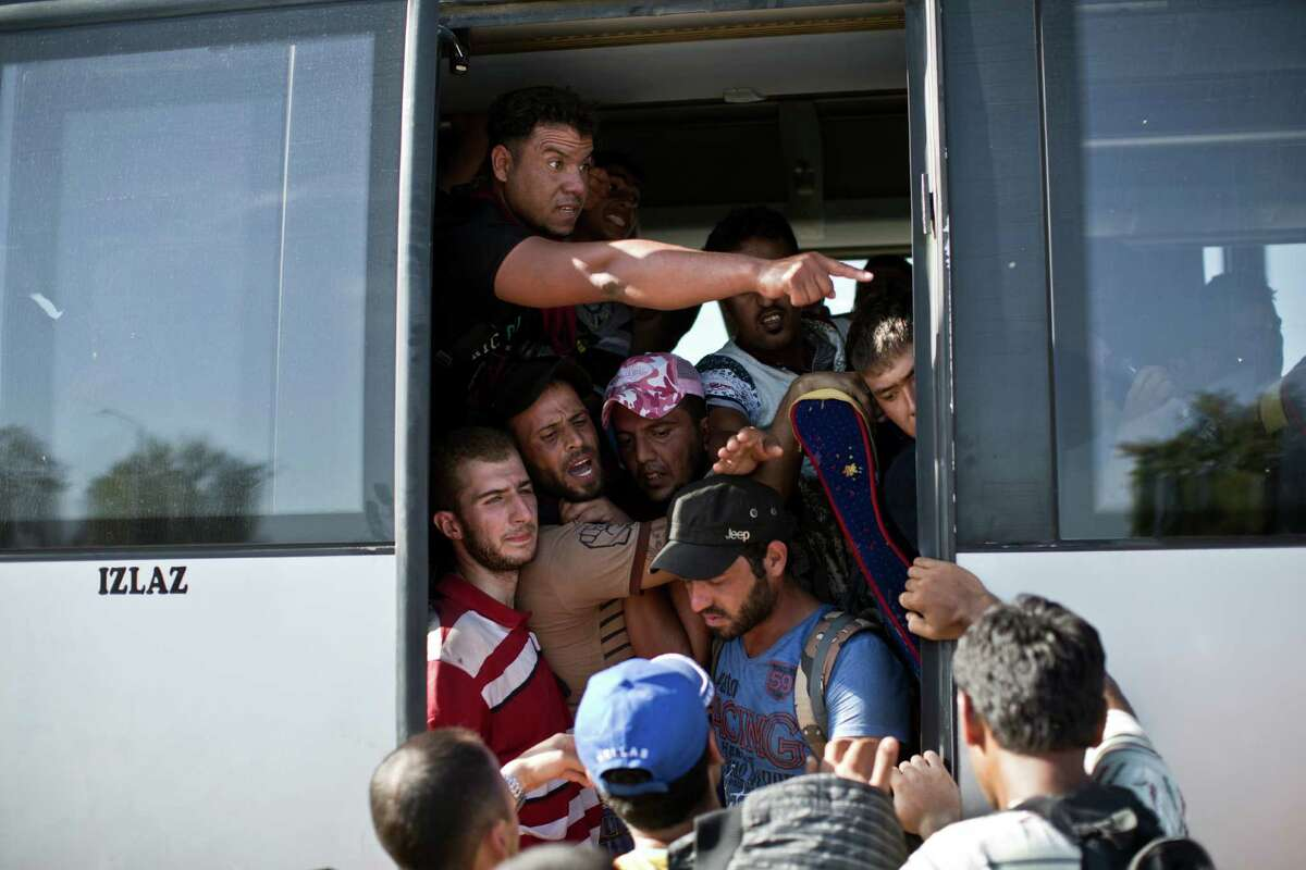 People crowd a bus provided by the Croatian government, after pushing through police lines in Tovarnik, Croatia, Thursday, Sept. 17, 2015. Hundreds of migrants have pushed through police lines in the eastern Croatian town of Tovarnik, with people trampling and falling on each other amid the chaos, as more than 2,000 men, women and children were stuck at the local train station for hours in blazing heat and sun on Thursday, waiting to board trains and buses for transport to refugee centers. (AP Photo/Marko Drobnjakovic) ORG XMIT: XMD113