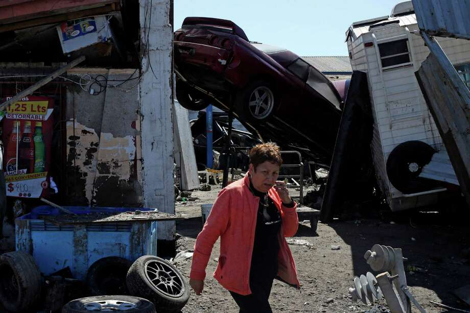 A woman walks past a car propped up between structures among the debris left behind by an earthquake-triggered tsunami in the coastal town of Coquimbo, Chile, Thursday, Sept. 17, 2015. Parts of this port city are a disaster zone after Wednesday night's 8.3-magnitude quake hit off the coast. (AP Photo/Luis Hidalgo) ORG XMIT: XLHP139 Photo: Luis Hidalgo / AP