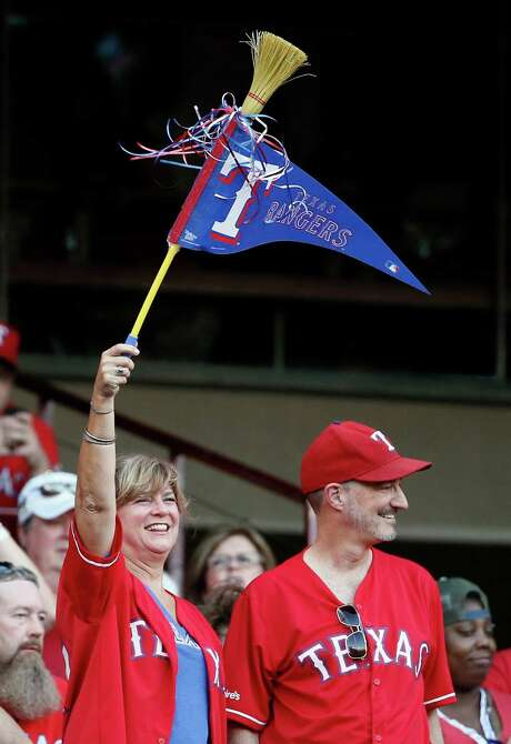 A fan waves a small broom with a Rangers flag, and that was even before Texas put the finishing touches on a sweep of a four-game series with the Astros. Photo: Tony Gutierrez, STF / AP