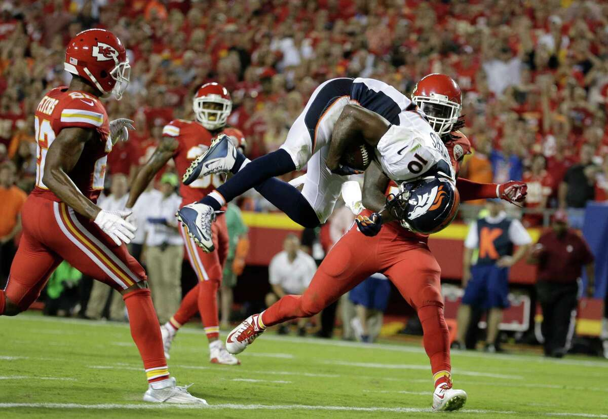 Denver Broncos wide receiver Emmanuel Sanders (10) does a somersault into the end zone for a touchdown between Kansas City Chiefs defensive backs Marcus Peters, left, Jamell Fleming (30) and Ron Parker, right, during the first half of an NFL football game in Kansas City, Mo., Thursday, Sept. 17, 2015. (AP Photo/Charlie Riedel) ORG XMIT: MONH127