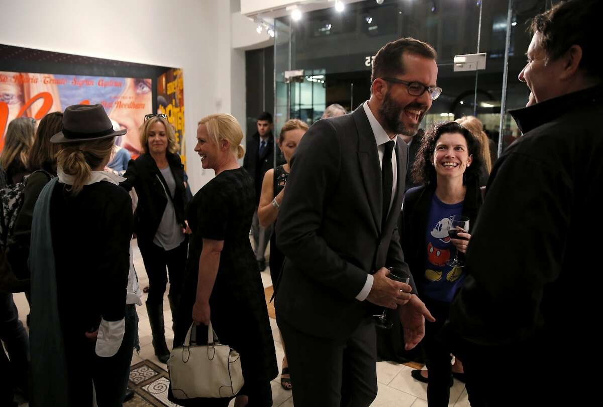 """Actress Patricia Arquette (left center) and Eric White (right center) entertain attendees of the U.S. premiere of White's """"New Works"""" exhibit at Serge Sorokko Gallery in San Francisco, California, on Thursday, Sept. 17, 2015."""