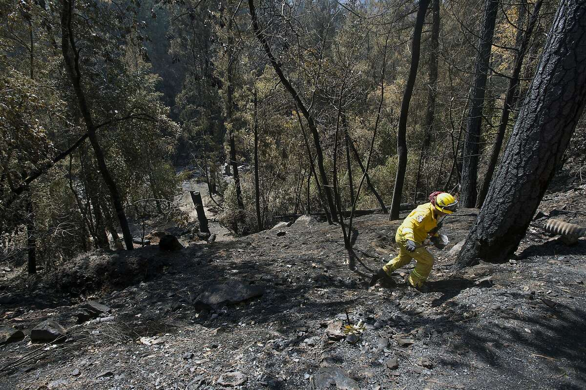 Matthew Wessell of Cal Fire Engine #3172 of Riverside climbs a scorched hillside checking for hot spots on Thursday, Sept. 17, 2015, in Anderson Springs, Calif. The Valley Fire that sped through Middletown and other parts of rural Lake County, less than 100 miles north of San Francisco, has continued to burn since Saturday despite a massive firefighting effort.