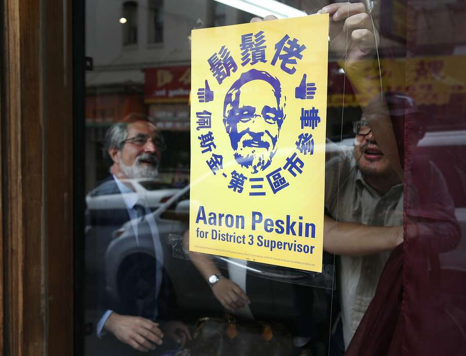 Aaron Peskin looks on as Alan Leong tapes a campaign poster inside his music shop on Jackson Street in Chinatown in San Francisco, Calif. on Thursday, Sept. 17, 2015. Peskin is seeking to unseat incumbent Julie Christensen in District 3 on the Board of Supervisors, a position he previously held from 2001-2009. Photo: Paul Chinn, The Chronicle