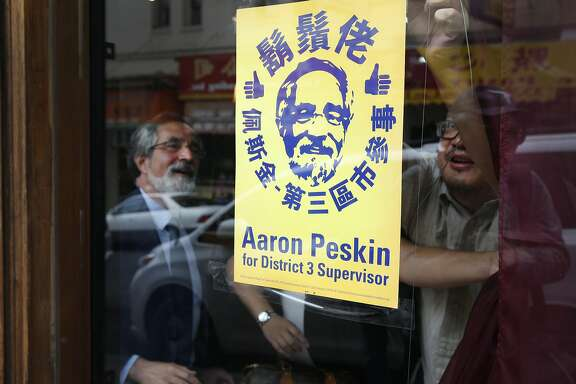 Aaron Peskin looks on as Alan Leong tapes a campaign poster inside his music shop on Jackson Street in Chinatown in San Francisco, Calif. on Thursday, Sept. 17, 2015. Peskin is seeking to unseat incumbent Julie Christensen in District 3 on the Board of Supervisors, a position he previously held from 2001-2009.
