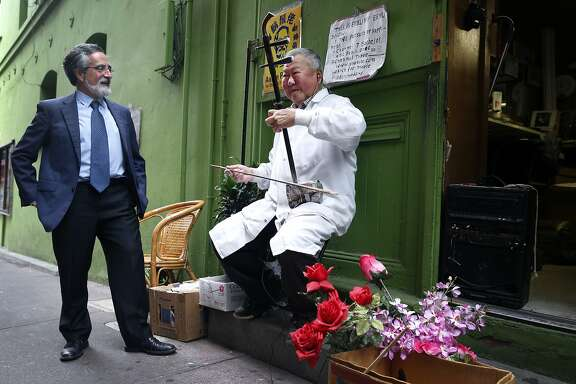 Barber Jun Yu plays an erhu for Aaron Peskin during a campaign stop on Chinatown's Ross Alley in San Francisco, Calif. on Thursday, Sept. 17, 2015. Peskin is seeking to unseat incumbent Julie Christensen in District 3 on the Board of Supervisors, a position he previously held from 2001-2009.