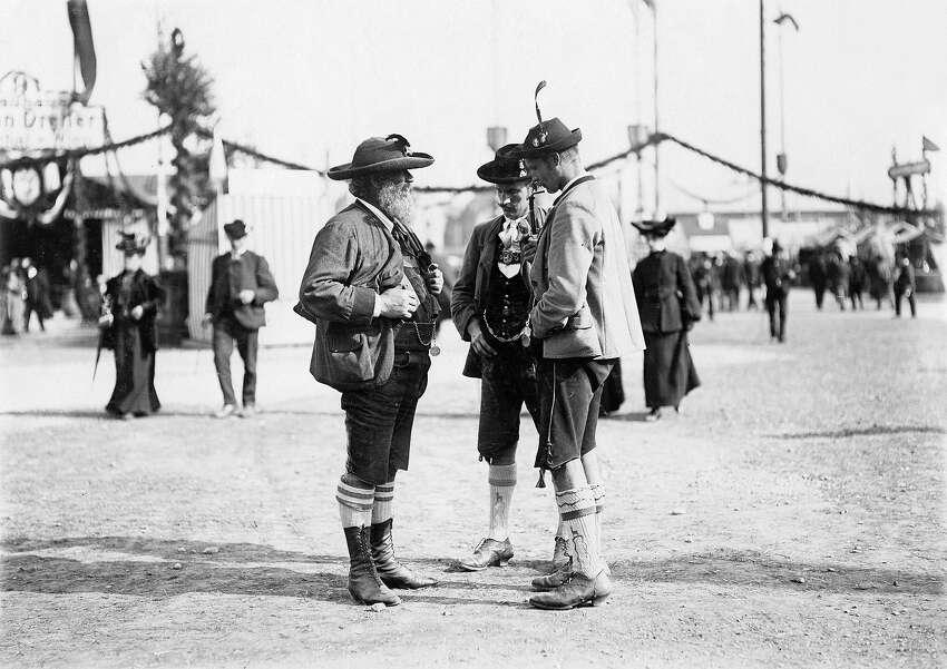 Three Bavarians wearing Lederhosen and traditional jackets and hats around 1910 at Oktoberfest.