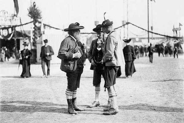 Three Bavarians wearing Lederhosen and traditional jackets and hats around 1910 at Oktoberfest.