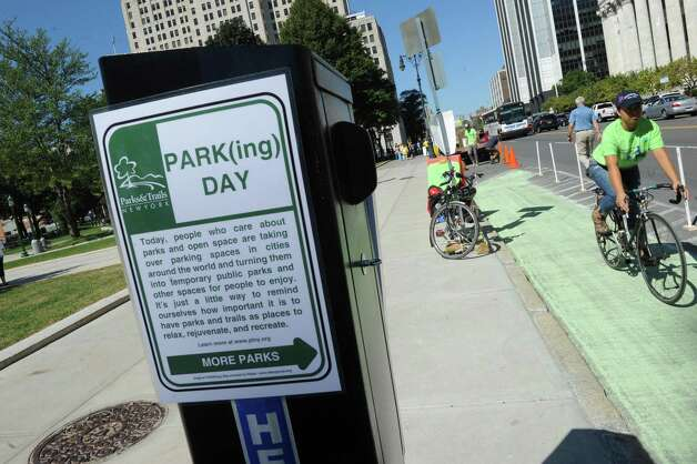 Rossana Coto-Batres, right, with Protected Bicycle Lane Coalition of Albany rides her bicycle in a created bike lane in a parking space on Washington Avenue as part of parking day on Friday Sept. 18, 2015 in Albany, N.Y.  (Michael P. Farrell/Times Union) Photo: Michael P. Farrell / 00033414A
