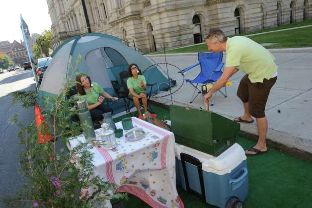 Left to right, Laura DiBetta, Robin Dropkin and Jonathan Duda of Parks and Trail New York set up a camp site in a parking space on Washington Avenue as part of parking day on Friday Sept. 18, 2015 in Albany, N.Y.  (Michael P. Farrell/Times Union) Photo: Michael P. Farrell / 00033414A