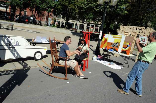 Albany Parking Enforcment officer Kendra McCalmon, seated right, takes a seat with Albany Center Gallery director Tony Iadicicco as artist Peter Leue takes their photograph in the Albany Center Gallery's both occupying a parking space on Broadway as part of parking day on Friday Sept. 18, 2015 in Albany, N.Y.  (Michael P. Farrell/Times Union) Photo: Michael P. Farrell / 00033414A