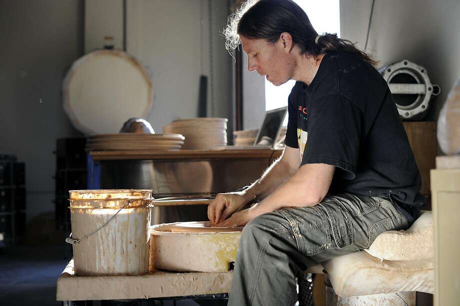"Ceramicist Travis McFlynn works on throwing a block of flame wear clay into a lid for a 5 quart dutch oven or ""bean pot"", for a restaurant client at his live/work space in Oakland, CA Thursday, September 17, 2015. Photo: Michael Short, Special To The Chronicle"