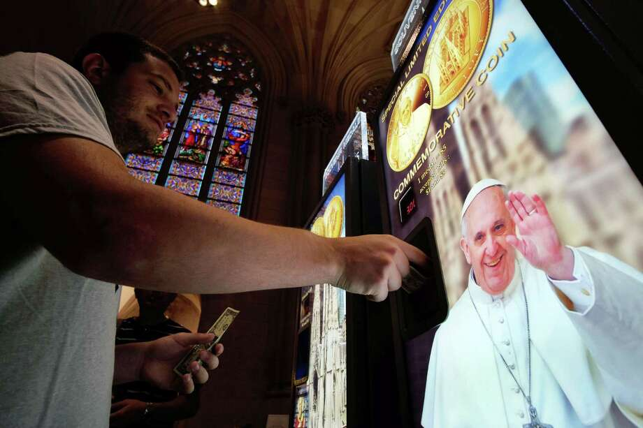 A man buys a souvenir medal with a picture of Pope Francis at a machine inside the Saint Patrick Cathedral in New York on August 28, 2015. Pope Francis will visit the US on September 22-27, stopping in Washington, DC, New York, and Philadelphia. AFP PHOTO/JEWEL SAMADJEWEL SAMAD/AFP/Getty Images ORG XMIT: 573957341 Photo: JEWEL SAMAD / AFP