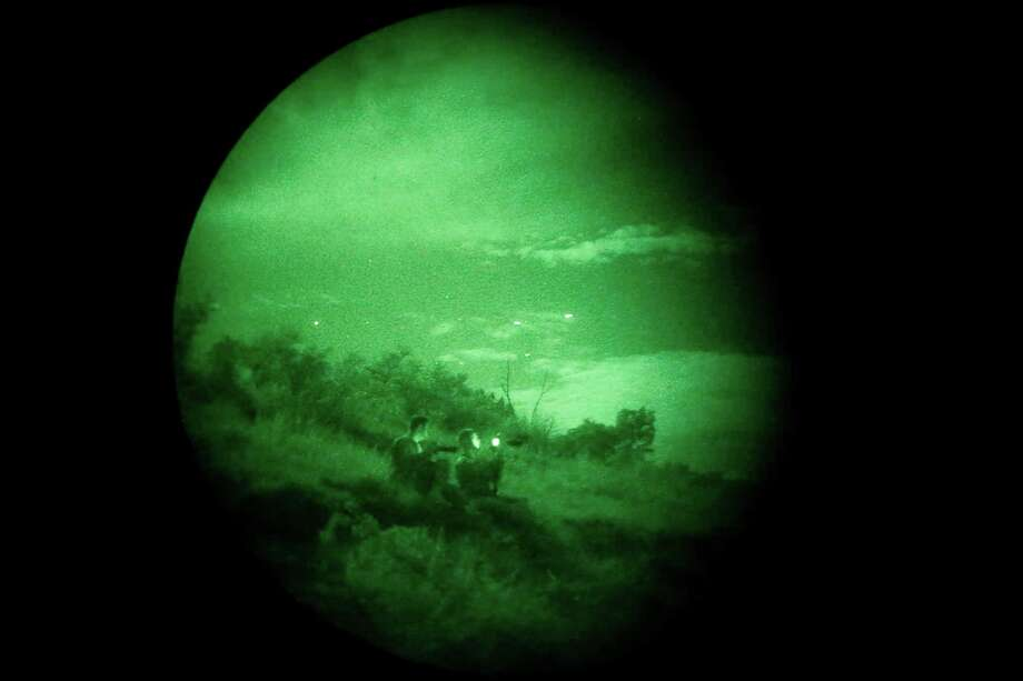 "FILE: As seen through night vision goggles, two enlisted officers from the U.S. Army Special Operations Public Affairs Office watch C-17 transports (seen as white dots in the sky) fly overhead around 11 p.m. on Tuesday, Aug. 26, 2015, as part of a special warfare training exercise held at Camp Bullis. The transports were carrying heavy equipment and paratroops and were expected to drop on a swath of land on the post but the mission was scrubbed at the last minute due to a technical issue. The exercises are a continuation of military exercises as some referred to as ""Jade Helm 15"" which started in July. Photo: Kin Man Hui /San Antonio Express-News / ©2015 San Antonio Express-News"
