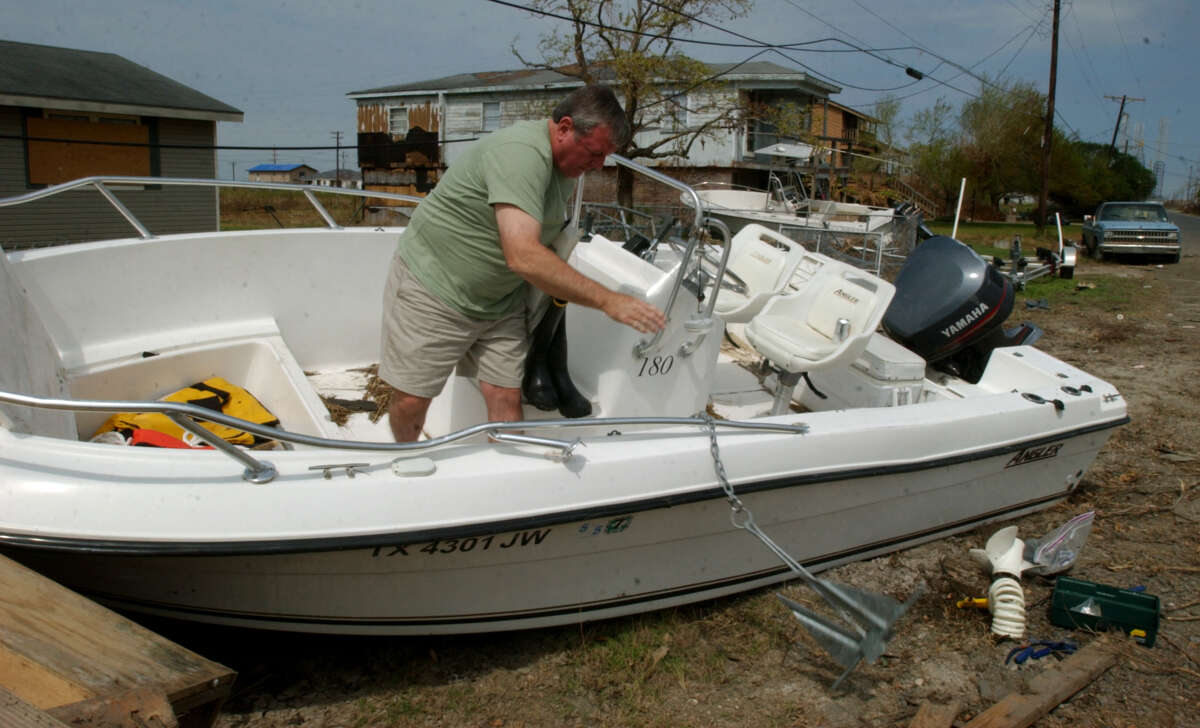 Ed Swift tossed the anchor overboard as he salvaged what he can from his boat in Sabine Pass. Swift's boat floated several blocks into someone's yard during Hurricane Rita.