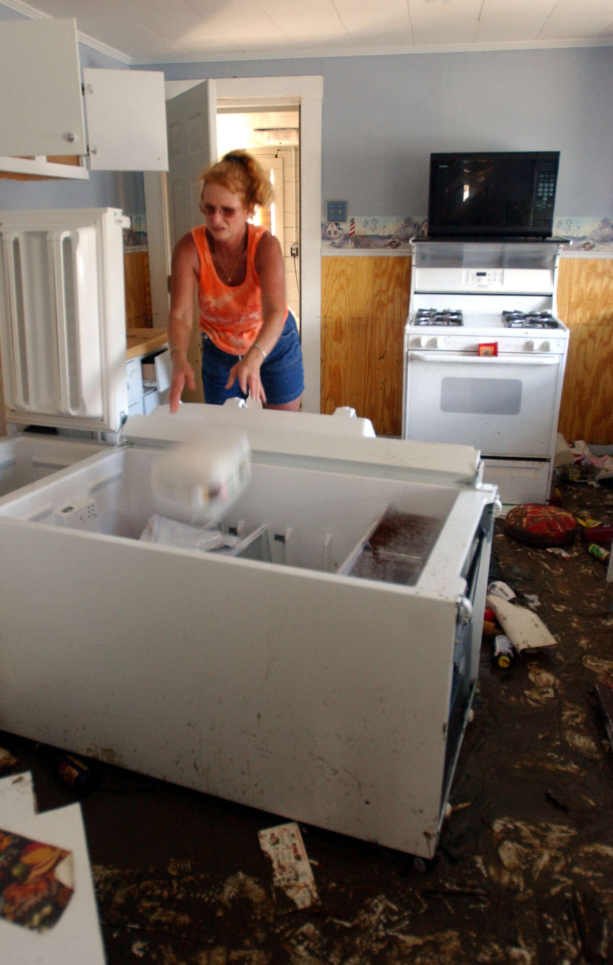 Glenda Eldridge tossed food from her cupboards into her refrigerator on Oct. 3, 2005, as she salvaged what she could from her home in Sabine Pass. Hurricane Rita hit the Gulf Coast town on Sept. 24, 2005, flooding the area and leaving more than 75 percent of the building uninhabitable.
