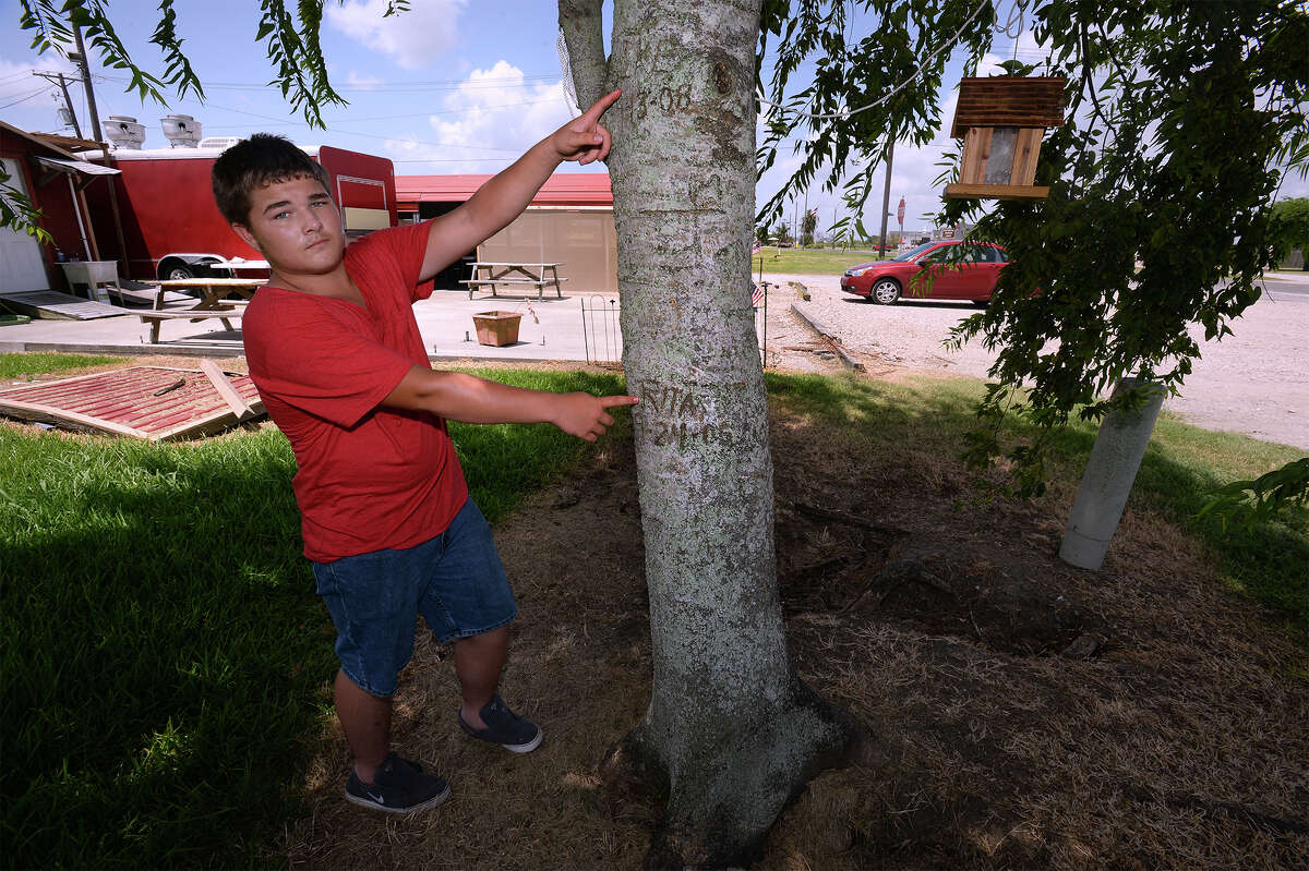 Kirk Blood, 14, son of Tammie Blood, points his right hand to the carved watermark indicating Hurricane Rita's water level in Sabine Pass. Blood's left hand points to the water level from Hurricane Ike in 2008. Tammie's Diner is pictured in the background.