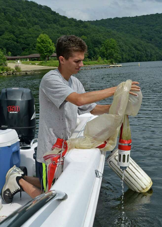 Former Western Connecticut State University biology student Jean-Luc Plante, who is now a graduate student at the University of Connecticut, takes a water sample from Lake Zoar during a 2013 field study to find evidence of zebra mussel presence. Photo: Contributed Photo / WCSU