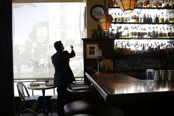 Trevor Noonan, floor manager, raises window coverings the morning after an employee unexpectedly quit while working at Absinthe Brasserie and Bar on Friday, September 18, 2015 in San Francisco, Calif.