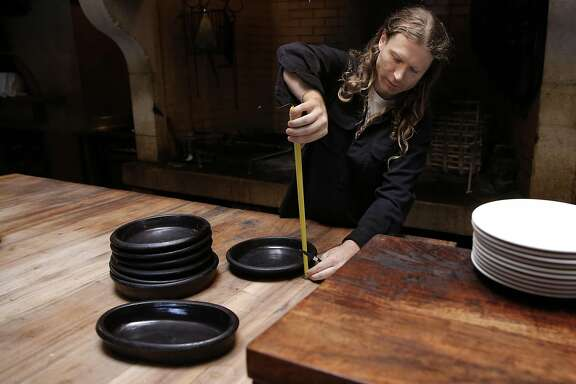 Flameware ceramics creator Travis McFlynn, takes measurements after meeting with Russell Moore, executive chef and owner of Camino restaurant, on Fri. September 18, 2015. Moore uses the custom created Flameware ceramics at his Camino restaurant in Oakland, Calif.