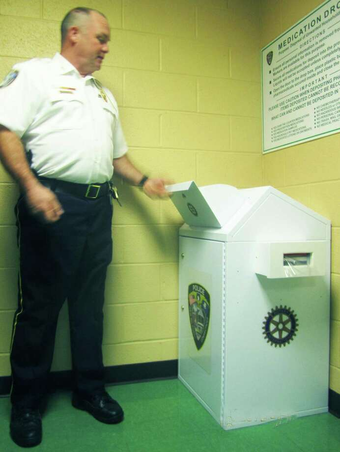 Police Chief Shawn Boyne demonstrates using the medication drop box at the New Milford Police Department. Boyne said more than 300 pounds of prescription medicines have been left in the box since the spring. Photo: File Photo / The News-Times